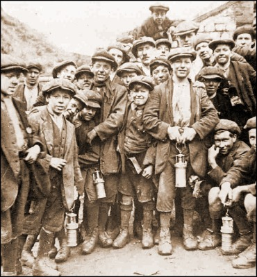 Young coal miners, some holding a Davy safety lamp